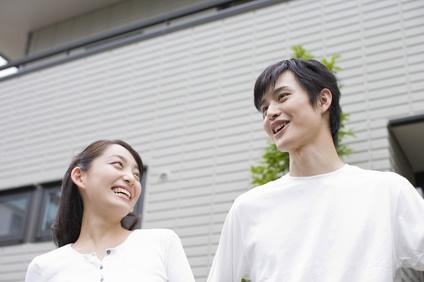 家の前で微笑むカップル