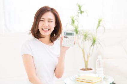笑顔の女性と電卓