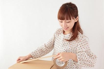 ガムテープで箱を閉じる女性