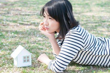 模型の家の前で頬杖をつく女性