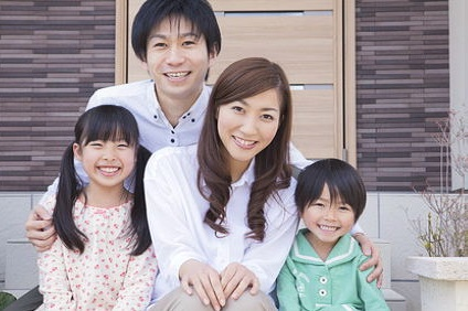 玄関前に座る家族