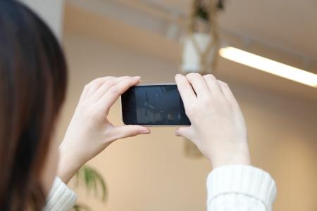 スマホで部屋の中を撮影する女性