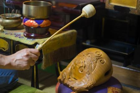 仏壇の前で読経をする僧侶
