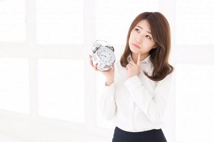 時計を持ち考える女性