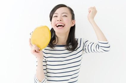 黄色い財布を持って喜ぶ女性