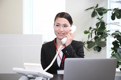 電話対応をする黒いスーツの女性