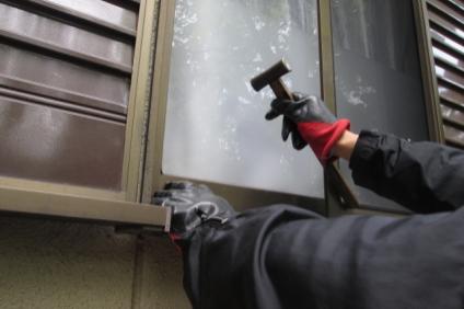 空き巣が窓を割ろうとしている