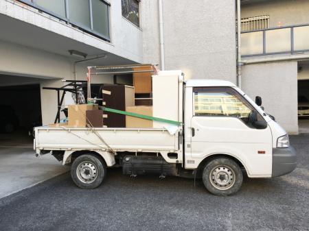 不用品を積んでいる便利屋のトラック